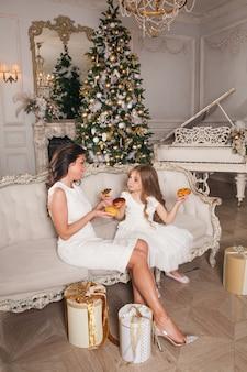 Gelukkig schattig meisje met mooie jonge moeder met plezier en donuts eten tegen de achtergrond van een versierde kerstboom in klassiek interieur. gelukkige familie in de feestelijke avond van het nieuwe jaar.