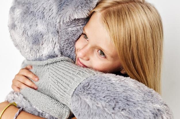 Gelukkig schattig meisje teddybeer in de handen van leuke geïsoleerde achtergrond