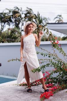 Gelukkig schattig romantisch blanke vrouw in zomer elegante witte open rug jurk, strooien hoed