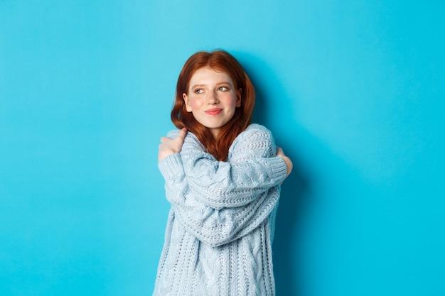 Gelukkig schattig roodharig meisje knuffelt zichzelf, draagt een comfortabele en warme trui, glimlacht naar de camera en staat op een blauwe achtergrond.