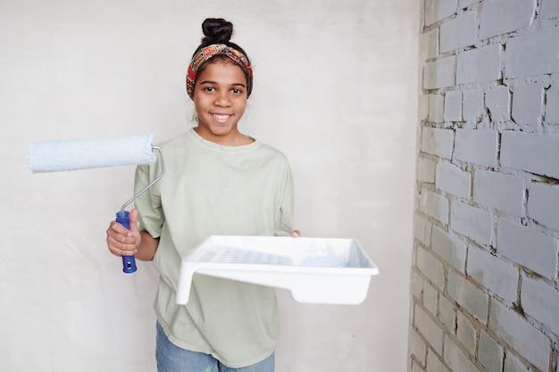 Gelukkig schattig tienermeisje met verfroller en witte vierkante plastic container met verf in de hoek bij twee muren van de woonkamer