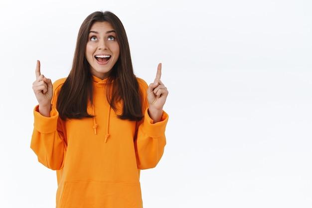 Gelukkig schattige brunette vrouw in oranje hoodie wijzend en opkijkend met een vrolijke uitdrukking, vond iets echt geweldigs en onderhoudends, staande enthousiaste witte muur