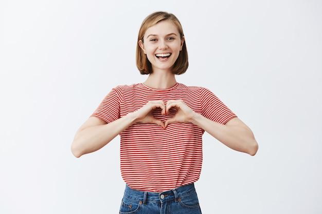 Gelukkig schattige jonge vrouw weergegeven: liefde gebaar, hart met vingers maken