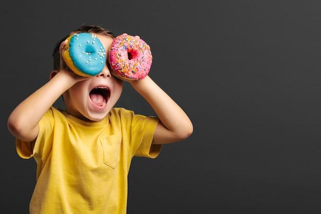 Gelukkig schattige jongen heeft plezier, gespeeld met donuts