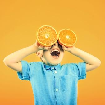 Gelukkig schattige jongen heeft plezier gespeeld met fruit oranje op gele oppervlakte muur. heldere foto van een jongen. gekleurde panoramafoto.