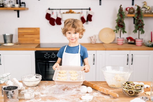 Gelukkig schattige jongen met rauwe zelfgemaakte koekjes die naar je kijken terwijl je aan de keukentafel staat