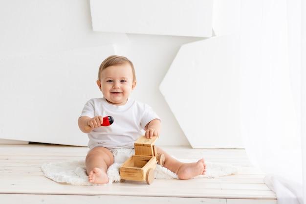 Gelukkig schattige kleine baby zes maanden oud in een wit t-shirt en luiers