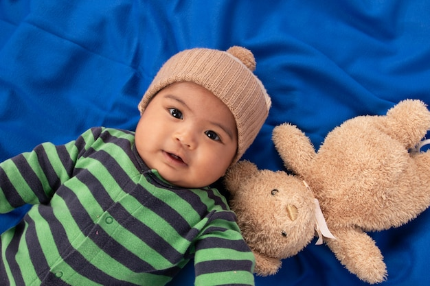 Gelukkig schattige kleine babyjongen liggend op blauwe deken en glimlachen