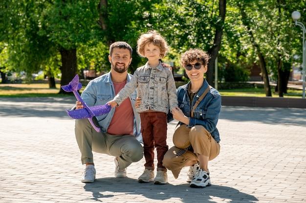 Gelukkig schattige kleine jongen en zijn aanhankelijke jonge ouders in vrijetijdskleding kijken naar jou terwijl ze tijd doorbrengen in openbaar park op zonnige dag