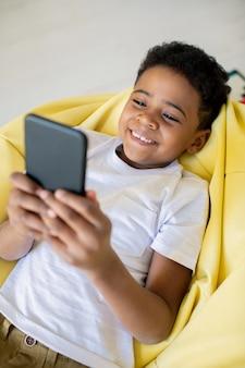 Gelukkig schattige kleine jongen met brede glimlach selfie maken, video kijken of communiceren voor smartphone terwijl u ontspant op de bank