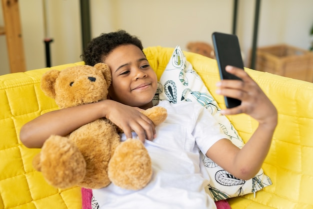 Gelukkig schattige kleine jongen van afrikaanse etniciteit met smartphone zijn teddybeer omarmen terwijl zittend op gele bank en selfie maken