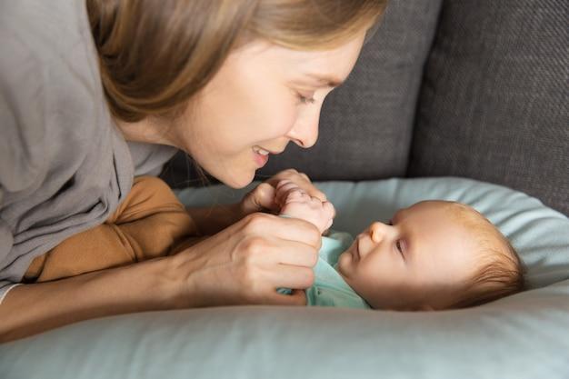 Gelukkig schattige nieuwe moeder praat met haar baby