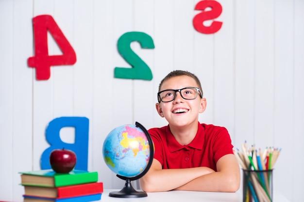 Gelukkig schattige slimme jongen zit aan een bureau in een bril met hand opheffen. het kind staat klaar om te antwoorden met een schoolbord