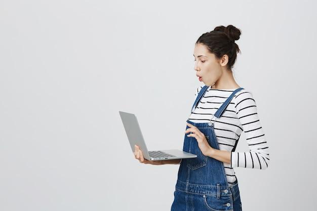 Gelukkig schattige vrouwelijke freelancer met behulp van laptop