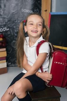 Gelukkig scholier in de klas met grote rugzak