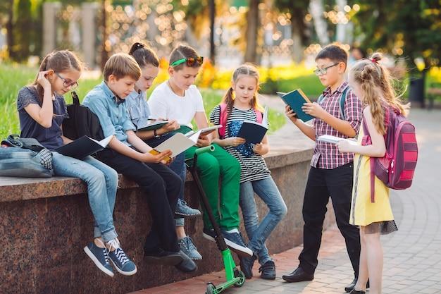Gelukkig schoolgenoten portret. schoolgenoten die met boeken in een houten bank in een stadspark zitten en op zonnige dag bestuderen.