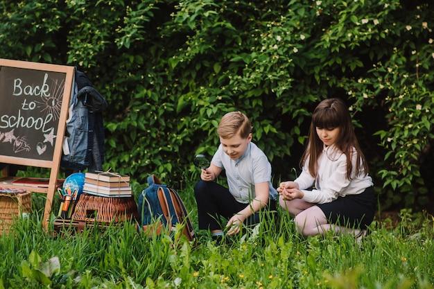 Gelukkig schooljongen en schoolmeisje onderzoekt de bloemen onder een vergrootglas