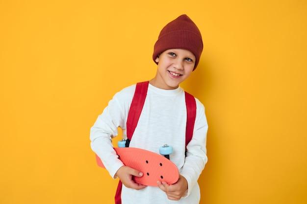 Gelukkig schooljongen in een rode hoed skateboard in zijn handen gele kleur achtergrond