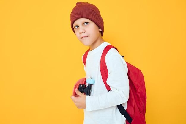 Gelukkig schooljongen in een witte trui skateboard entertainment geïsoleerde achtergrond