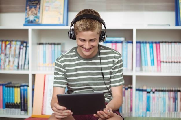 Gelukkig schooljongen luisteren muziek tijdens het gebruik van digitale tablet in bibliotheek