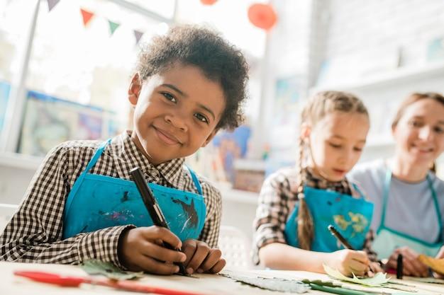 Gelukkig schooljongen met markeerstift op zoek naar jou zittend door bureau op les op achtergrond van klasgenoot en leraar
