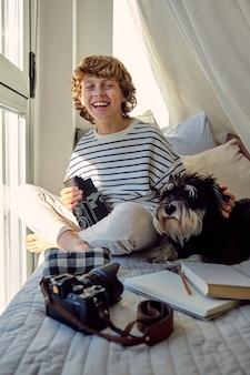 Gelukkig schooljongen met oude fotocamera en hond op bed