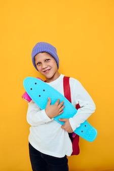 Gelukkig schooljongen met rode rugzak blauwe skateboard studio levensstijl