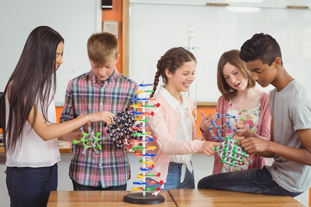 Gelukkig schoolkinderen experimenteren molecuul model in laboratorium