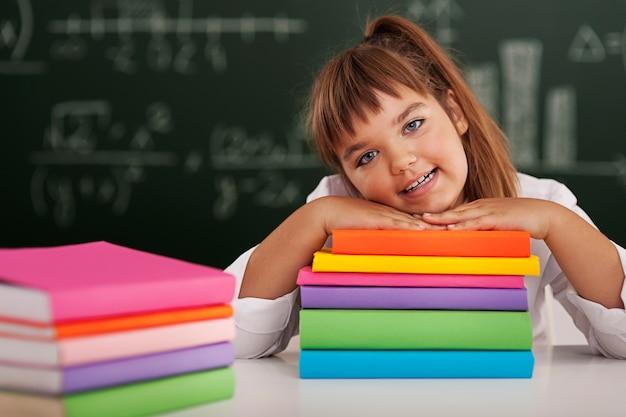 Gelukkig schoolmeisje dat op haar boeken leunt