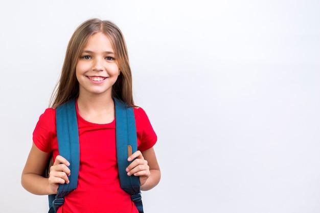 Gelukkig schoolmeisje die met rugzak bij camera glimlachen