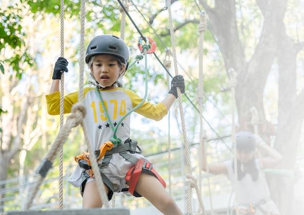 Gelukkig schoolmeisje die van activiteit in een avonturenpark genieten