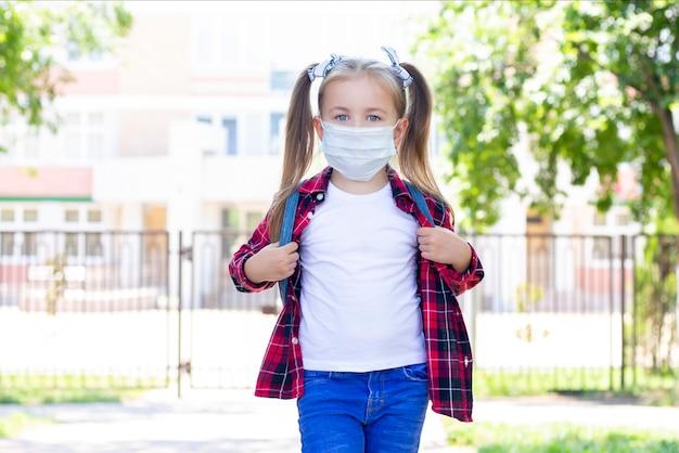 Gelukkig schoolmeisje in beschermend masker met een rugzak