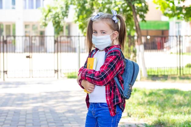 Gelukkig schoolmeisje in een beschermend masker met een rugzak en een leerboek in haar handen. in een wit t-shirt en een geruit overhemd