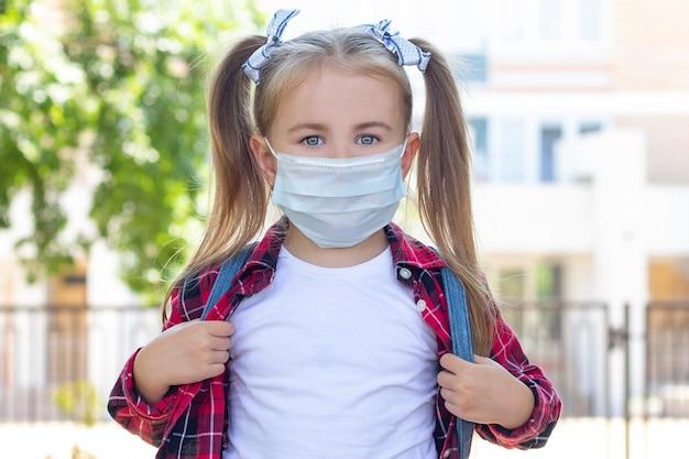 Gelukkig schoolmeisje in een beschermend masker met een rugzak. in een wit t-shirt en een geruit overhemd