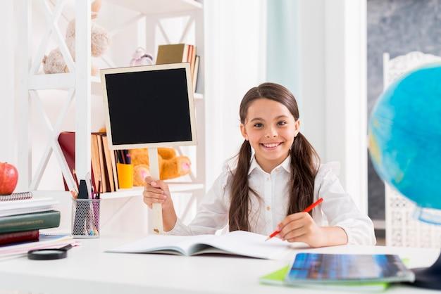 Gelukkig schoolmeisje in uniform studeren aan de klas