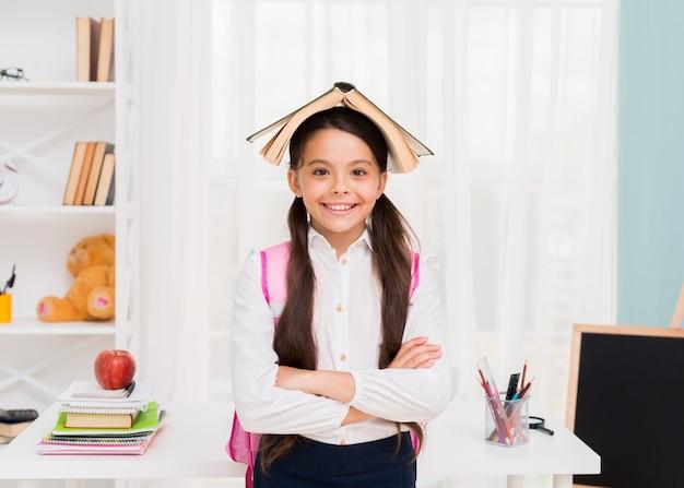 Gelukkig schoolmeisje met boek op hoofd