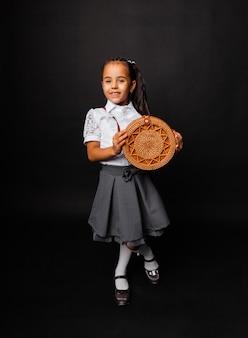 Gelukkig schoolmeisje met een ronde rieten tas geïsoleerd op een donkere achtergrond.