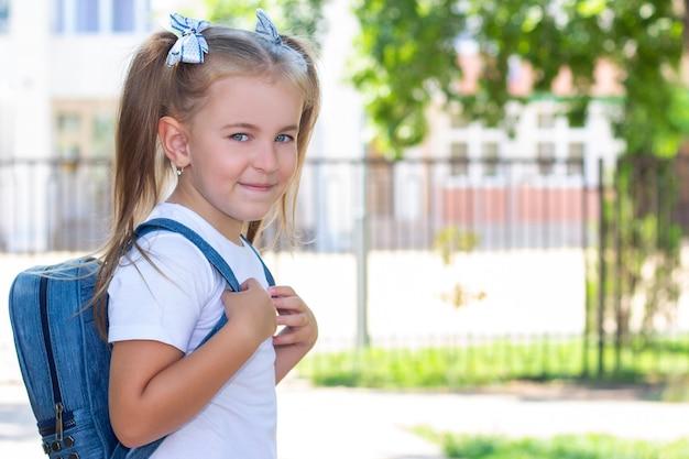 Gelukkig schoolmeisje met een rugzak in een wit t-shirt. op straat