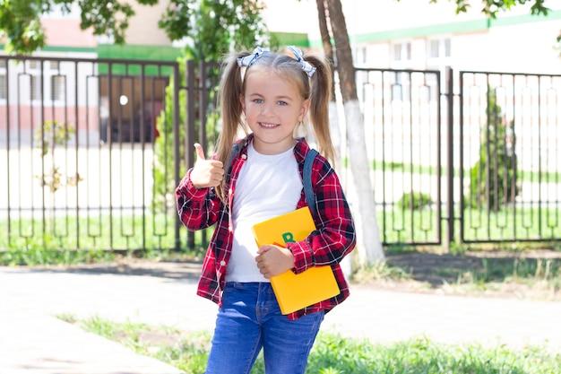 Gelukkig schoolmeisje met een rugzak laat zien. in een wit t-shirt en een geruit overhemd