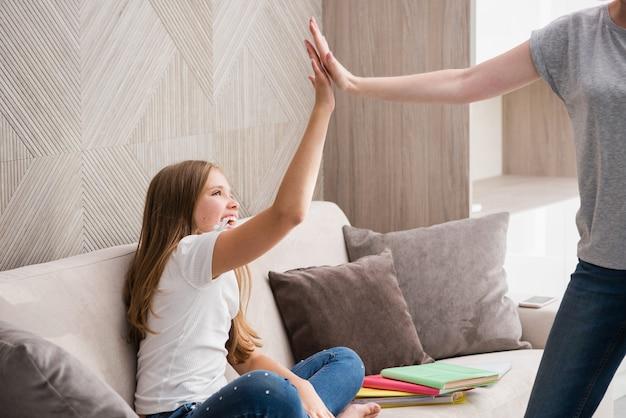 Gelukkig schoolmeisje neemt high five met volwassen vrouw