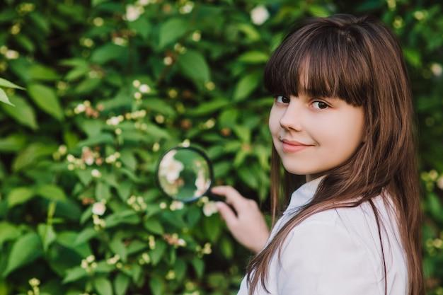 Gelukkig schoolmeisje onderzoekt de bloemen onder een vergrootglas