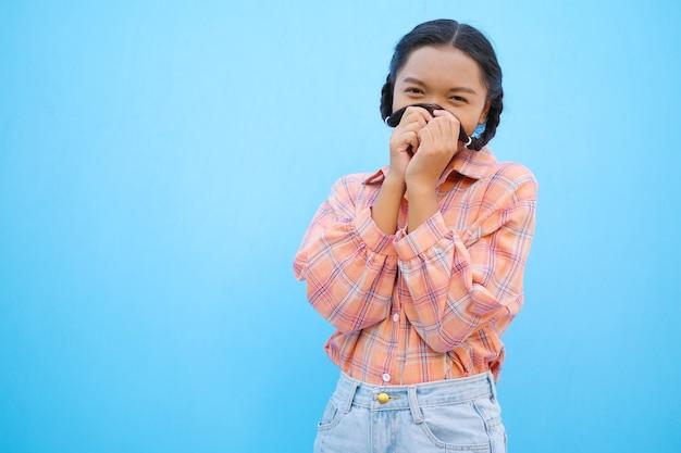 Gelukkig schoolmeisje op blauwe achtergrond aziatisch meisje