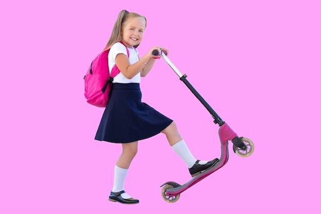 Gelukkig schoolmeisje op een scooter met een rugzak. isoleren op roze achtergrond