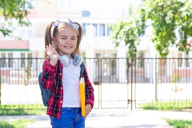 Gelukkig schoolmeisje op straat met een leerboek in haar handen, zwaaiend met haar hand. met koptelefoon om zijn nek staat op straat bij de school