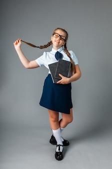 Gelukkig schoolmeisje permanent met boek in handen, geïsoleerd op een grijze achtergrond