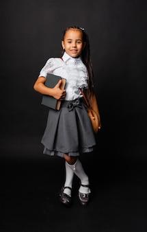 Gelukkig schoolmeisje permanent met een boek in haar handen, geïsoleerd op een donkere achtergrond.