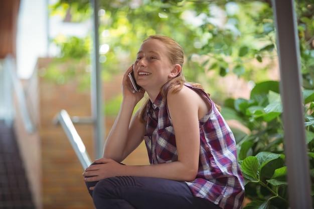 Gelukkig schoolmeisje praten op mobiele telefoon