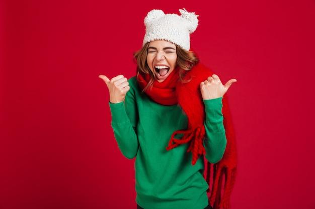 Gelukkig schreeuwende brunette vrouw in trui, grappige muts en sjaal