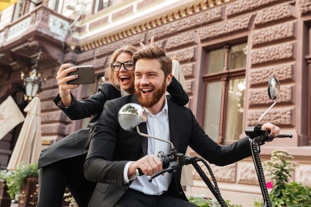 Gelukkig schreeuwende stijlvolle paar zittend op moderne motor buitenshuis