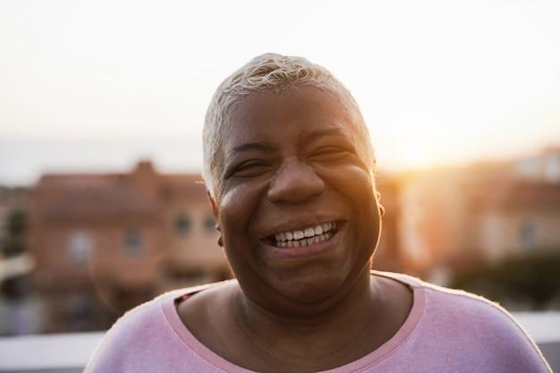 Gelukkig senior afrikaanse vrouw die lacht op camera buiten in de stad